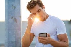 Sportive ung man i staden med smartphonen royaltyfri bild