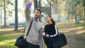 Sportive ungdomartar för lyckliga vänner selfie genom att använda smartphonen, efter utomhus- övning har parkerat in Mannen och k stock video