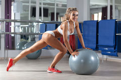 Sportive woman with a ball in the gym Royalty Free Stock Photo