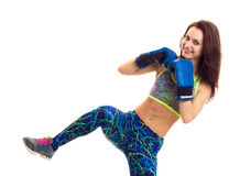 Sportive woman in boxing gloves. Sportive young woman with brown long hair wearing in colored sports top and blue leggins with blue boxing gloves fighting on Royalty Free Stock Photography