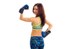 Sportive woman in boxing gloves. Young sportive woman with long brown hair wearing in colored sports top and blue leggins with blue boxing gloves on white Stock Photos
