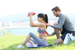 Sportive woman with coach doing excercises outdoors. Fitness girl with coach working out in outdoor park Stock Image