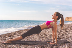Sportive woman doing plank on the beach Royalty Free Stock Images