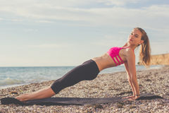 Sportive woman doing plank on the beach Stock Images