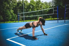Sportive woman doing push-ups on the blue tennis court in Moscow Yauza park stock photo