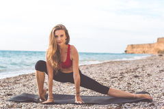 Sportive woman doing yoga poses on the beach Stock Photography
