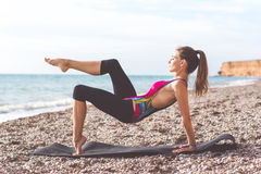 Sportive woman doing yoga poses on the beach Stock Images