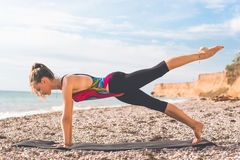 Sportive woman doing yoga poses on the beach Royalty Free Stock Images