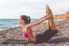 Sportive woman doing yoga poses on the beach Royalty Free Stock Photography