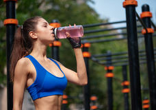 Sportive woman drinking vitamin water at the street gym Royalty Free Stock Images