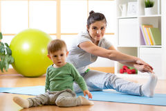 Sportive woman is engaged in fitness and yoga at home. Her son kid by near sitting and playing. Royalty Free Stock Photography