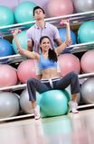 Sportive woman exercises in fitness gym Stock Photos