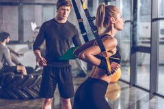 Sportive woman exercising with trx gym equipment with trainer near by. Side view of sportive women exercising with trx gym equipment with trainer near by Royalty Free Stock Photo