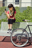 Sportive woman with fixie bike looking smartphone Royalty Free Stock Photography