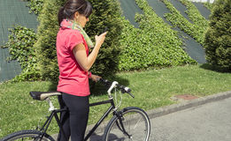 Sportive woman with fixie bike looking smartphone Stock Photography