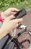 Sportive woman with fixie bike looking smartphone Stock Photos