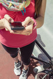 Sportive woman with fixie bike looking smartphone Stock Images