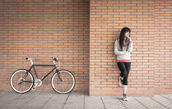 Sportive woman with fixie bike over a brick wall Royalty Free Stock Image