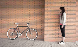 Sportive woman with fixie bike over a brick wall Stock Photography