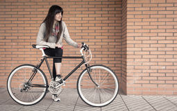 Sportive woman with fixie bike over a brick wall Stock Images