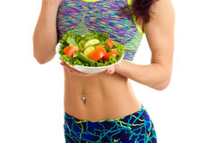 Sportive woman holding salad. Sportive young woman with long brown hair wearing in colored sports top and blue leggins holding white plate with green salad and Royalty Free Stock Photos