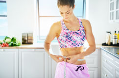 Sportive woman holding tape-measure round her waist. Young muscular woman measuring her waistline with tape in the kitchen. Horizontal indoors shot Stock Photos