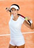 Sportive woman keeps tennis racket on shoulders Royalty Free Stock Image