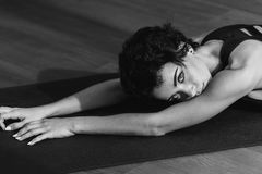Sportive woman laying on yoga mat royalty free stock image