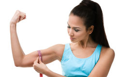 Sportive woman measures her bicep. With  measuring tape, isolated on white Stock Image