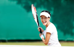 Sportive woman plays tennis Stock Photography