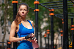 Sportive woman posing with bottle of water at the street gym Stock Photos