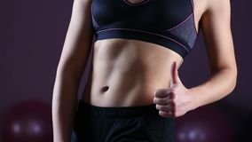 Sportive woman proudly demonstrating ideal flat belly, making thumbs-up sign