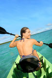Sportive woman rowing in kayak. Back view of beautiful woman paddling in canoe stock image