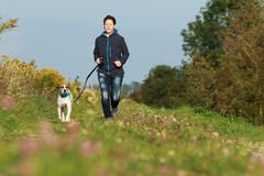 Sportive woman runs with her dog in autumn. Sportive woman runs with her dog on a leash in autumn exterior shot Royalty Free Stock Image