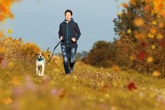 Sportive woman runs with her dog in autumn. Sportive woman runs with her dog on a leash in autumn exterior shot Stock Photos