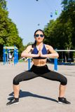 Sportive woman on sport playground. Young sportive woman in a bright blue sport bra, black leggings and dark sunglasses making exercises on the sport playground Royalty Free Stock Photos