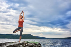 Sportive woman standing on the rock and practicing yoga against river. Stock Image