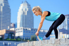 Sportive woman stretching her leg muscles Stock Images