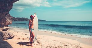Sportive woman with surfboard. On beautiful sandy coast, active hobby, waiting for a good waves, enjoying summer vacation on the beach stock photos