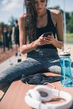 Sportive woman using smartphone. Portrait of sportive women using smartphone while resting after training on bench Stock Photo