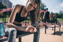 Sportive woman using smartphone. Portrait of sportive women using smartphone while resting after training on bench Stock Photography
