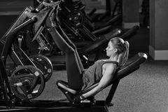 Sportive woman using weights press machine for legs. Gym. Sportive woman using weights press machine for legs at the gym. Pretty brunette exercising in a Royalty Free Stock Image
