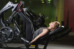 Sportive woman using weights press machine for legs. Gym. Stock Images