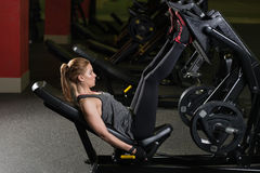 Sportive woman using weights press machine for legs. Gym. Stock Photos