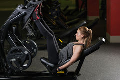 Sportive woman using weights press machine for legs. Gym. Royalty Free Stock Photos