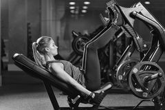 Sportive woman using weights press machine for legs. Gym. Stock Photography
