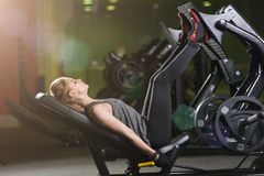 Sportive woman using weights press machine for legs. Gym. Royalty Free Stock Photography