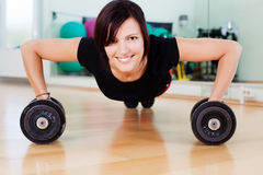 Sportive woman. Very sportive woman doing pushups with dumbbells in a gym Royalty Free Stock Photo
