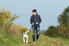 Sportive woman walks her dog in autumn. Sportive woman walks her dog on a leash in autumn exterior shot Royalty Free Stock Photos