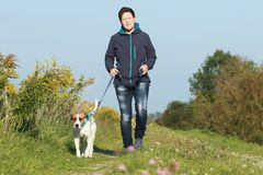 Sportive woman walks her dog in autumn. Sportive woman walks her dog on a leash in autumn exterior shot Stock Photos